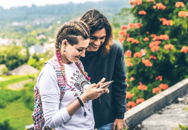 woman showing a Pisces man how creative she is with a cell phone.