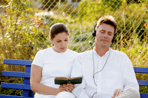 couple sitting on bench while woman is giving her Aries man space to listen to music on his headphones