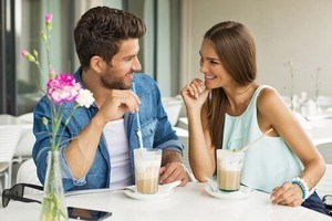Aquarius man talking to a woman seated at a table drinking coffee