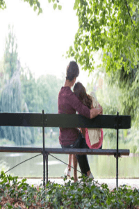 man with his arm around a woman sitting on a park bench