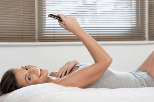 woman lying on a bed smiling and reading a text message to her Cancer crush