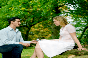 man down on one knee presenting a ring to a woman