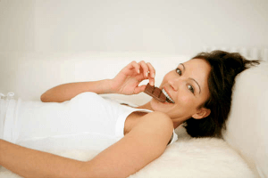 woman lying back smiling and eating chocolate