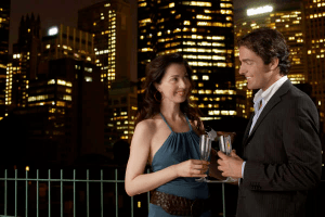 couple dringing champagne in front of brightly lit buildings