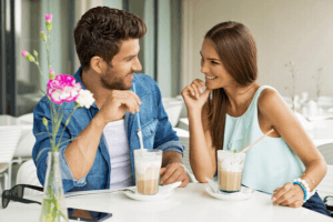 couple sitting in cafe flirting over a cup of coffee