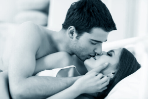 man kissing woman on bed while stroking her cheek