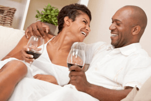 man with arm around woman laughing over glasses of wine