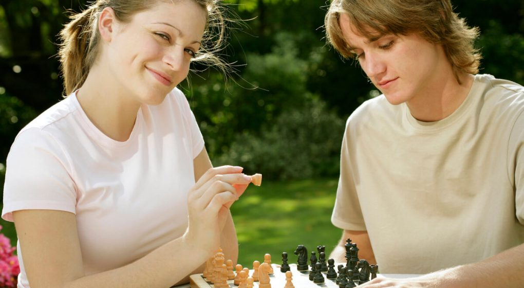woman smiling as she plays chess with her boyfriend.