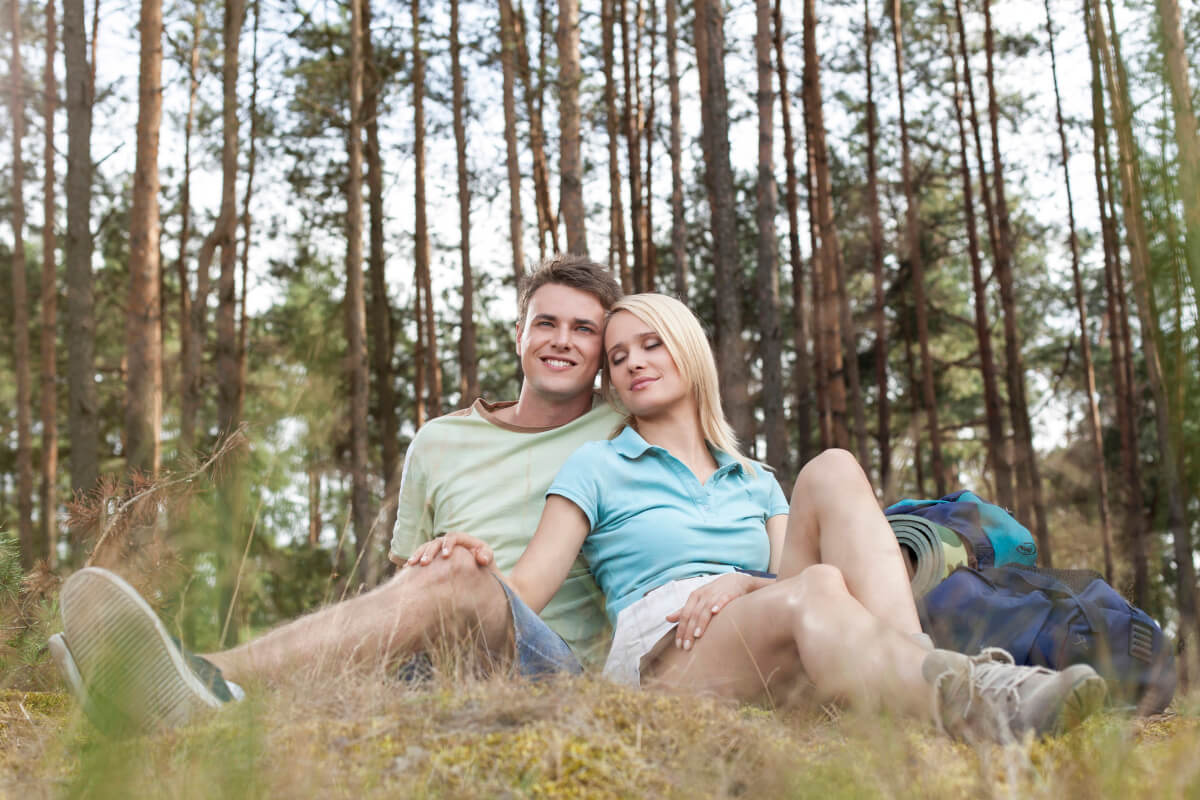 couple resting in a forest of trees