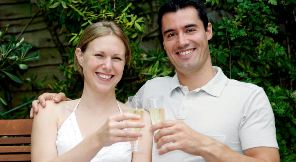 couple sitting on a garden bench drinking wine