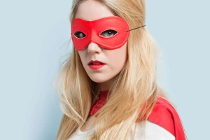 Blond woman with red eye mask