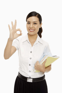 woman smiling as she makes ok sign with thumb and forefinger