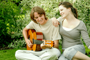 Gemini man playing guitar while woman leans on his shoulder