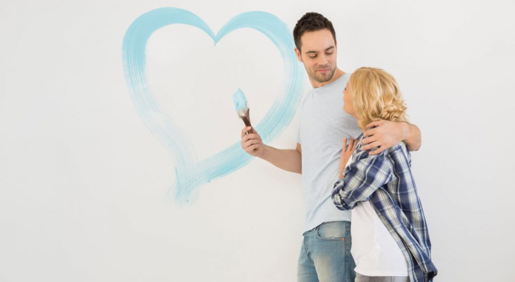 Man with his arm around a woman drawing a heart on a wall