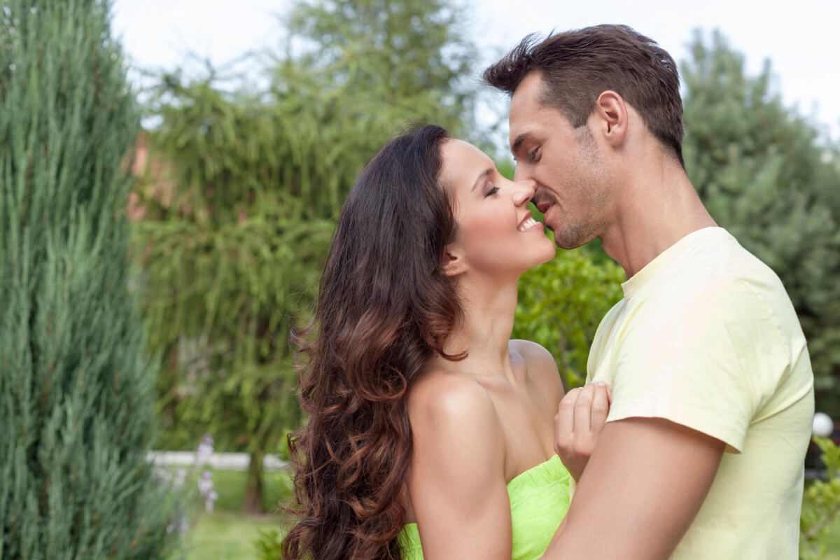 Couple about to kiss in a garden