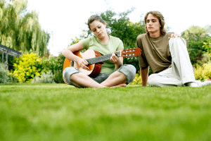 woman sitting on grass while playing guitar and watched by man