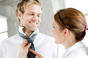 man smiling as woman knots his tie
