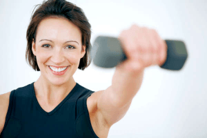 smiling woman holding a dumbell in her left outstretched hand