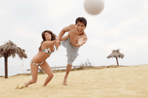 couple on a beach playing netball