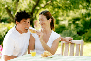 couple laughing as they sit at a table and the girl feeds the man a piece of cake