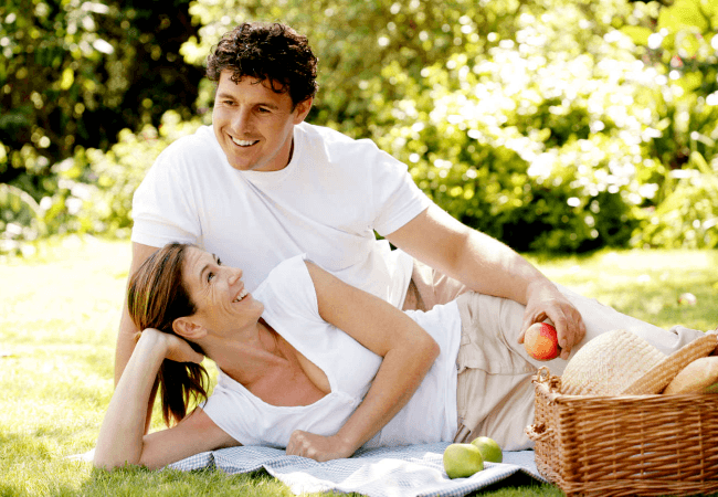 couple laying an the grass eating a picnic