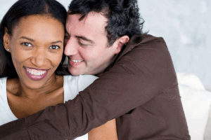 Black girl being cuddled by white man both are smiling