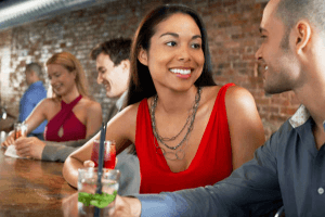 Girl in red dress sitting at a bar having a drink with a man