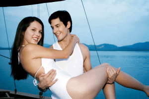 a man lifting an attractive woman off her feet while aboard a ship