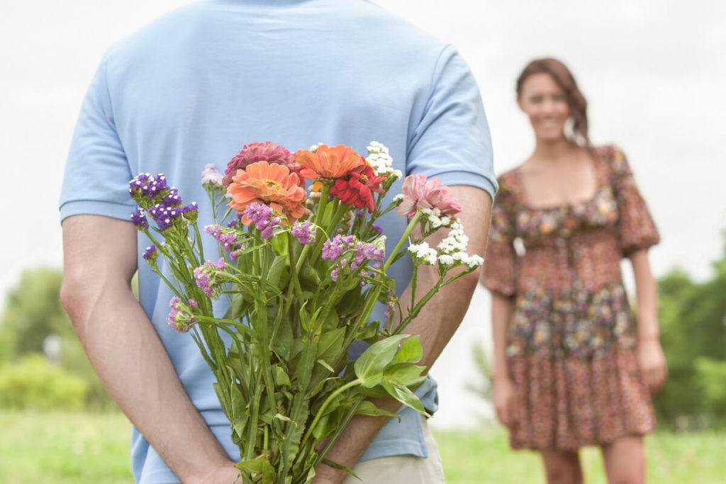 man with flowers behind his back in front of woman