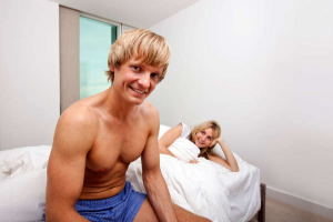 Man in shorts sitting on a bed watched by a woman in bed