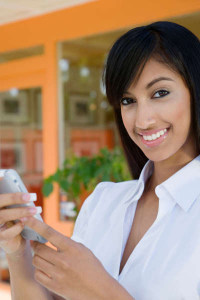 smiling woman using her cell phone to check for text messages