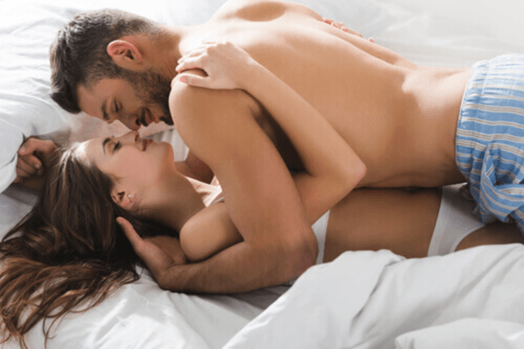 man kissing a woman in bed