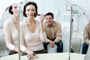 man sitting on bed watching a woman put her make up on in front of a mirror