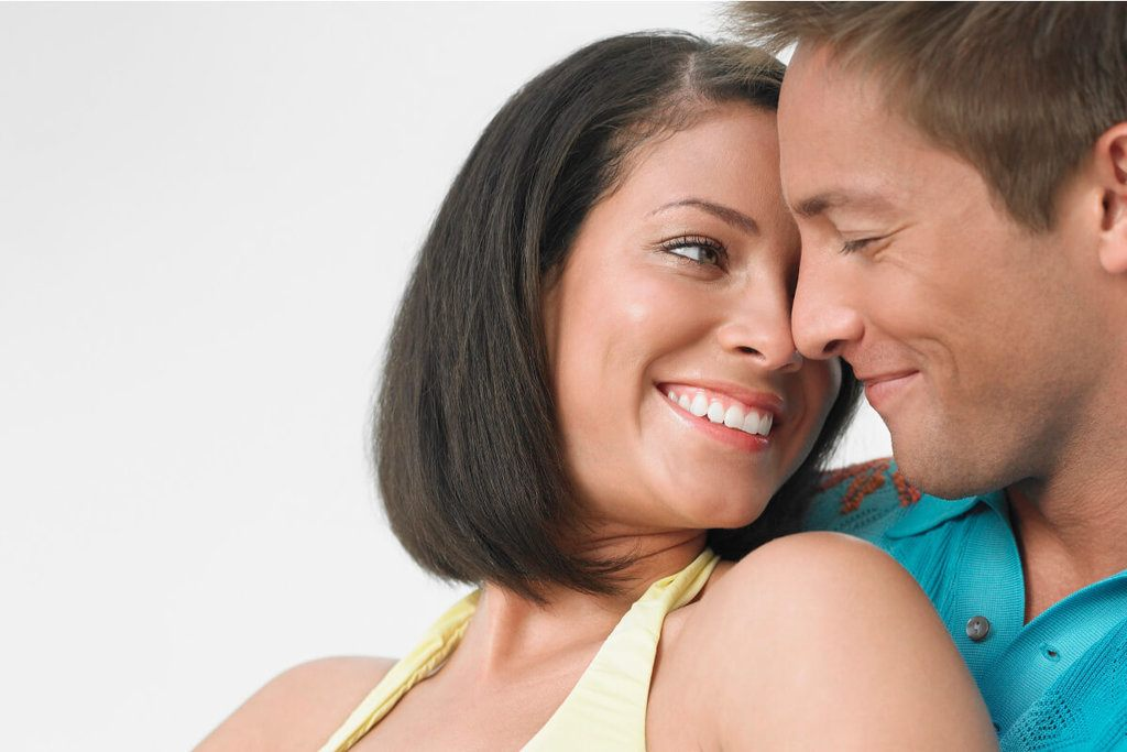 smiling woman about to kiss man
