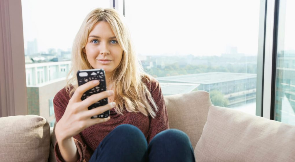 woman sitting on a couch with a cell phone