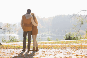 couple with arms around each other while they look at a stunning view