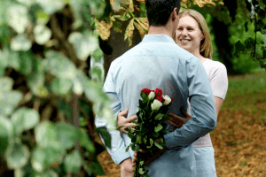 couple together with man with bunch of flowers behind his back