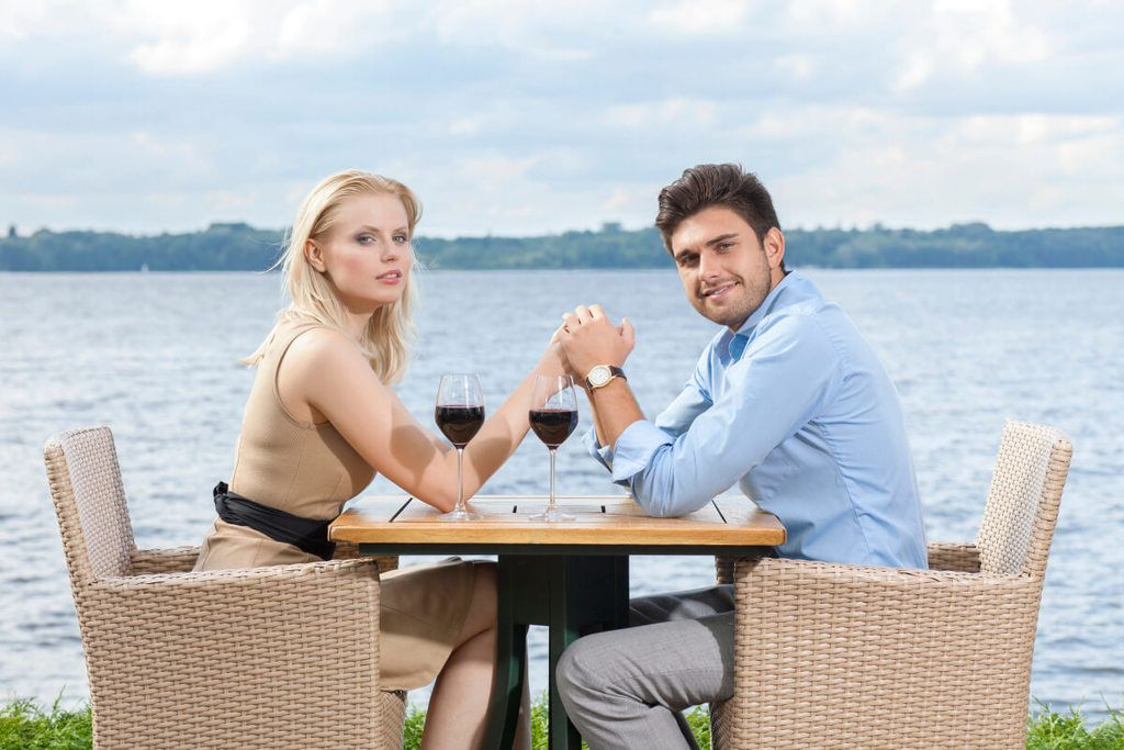 A man and woman holding hands across a table as they drink red wine