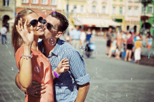 Cancer man kissing a smiling woman in a market setting