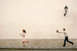 man with a bunch of flowers chasing a woman