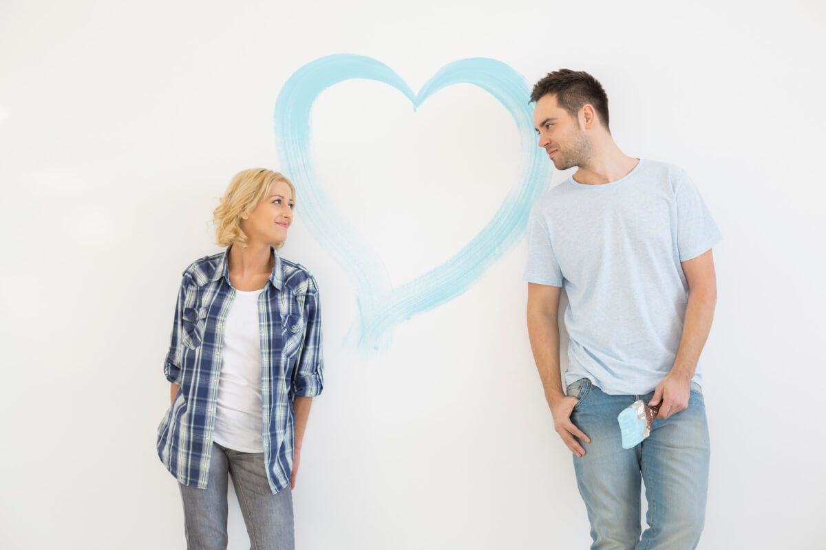 man painting a heart on a wall to show his love to his girlfriend