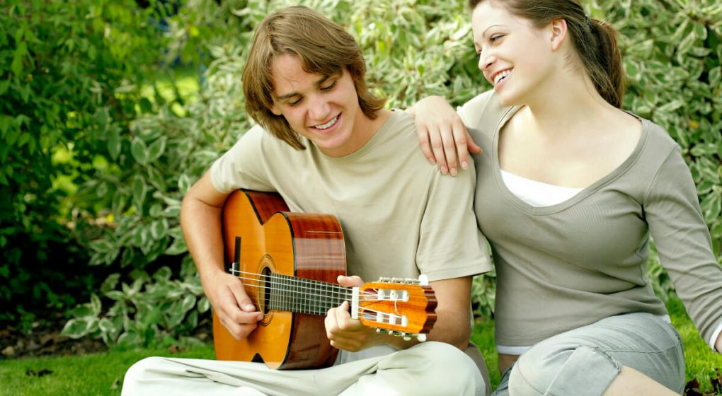 woman smiling as she listens to her guy playing guitar