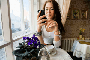 woman sitting at a table using her cell phone to text