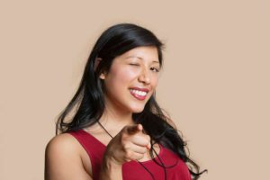 Smiling girl winking and pointing her finger confidently
