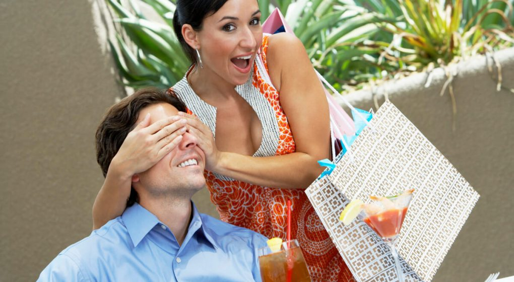 woman surprizing a man by covering his eyes with her hands
