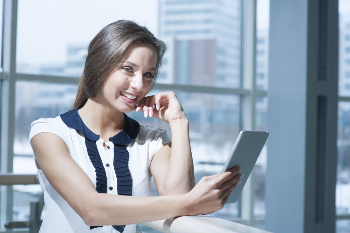 woman smiling as she looks at an ipad