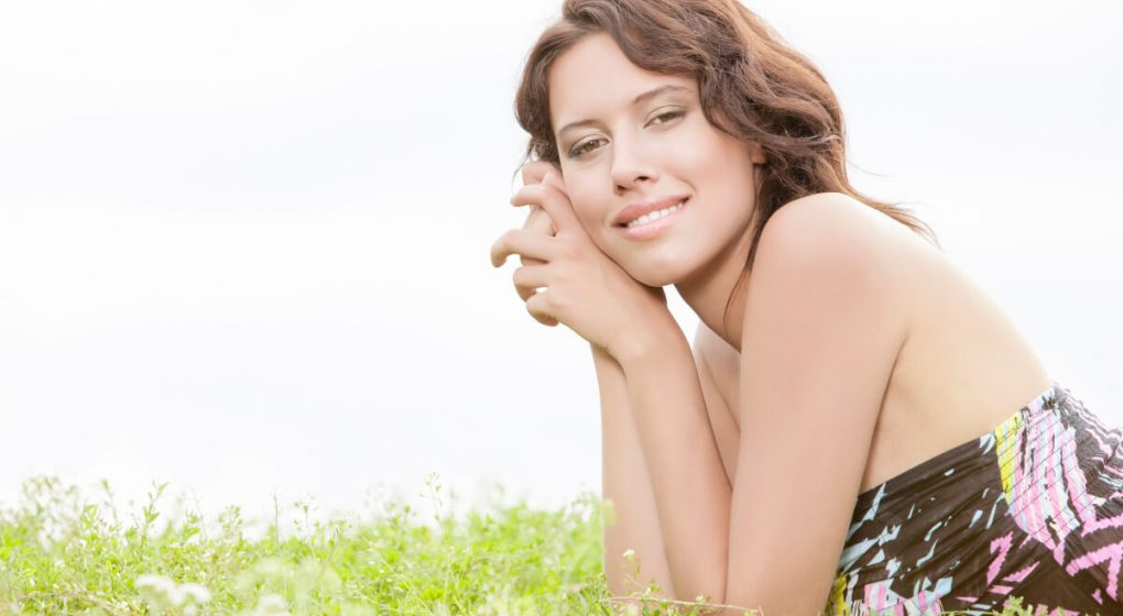 Woman lying down with her elbows on the grass