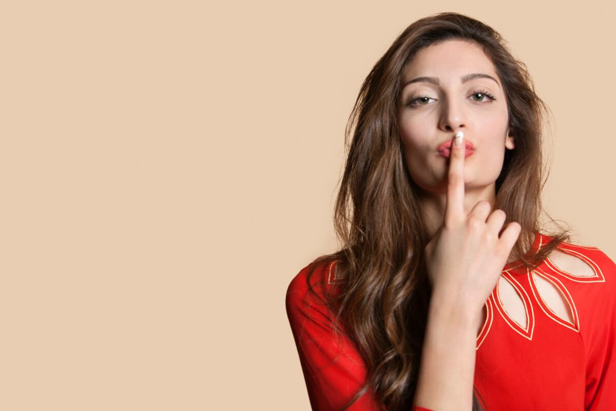 woman in red dress putting her finger to her lips