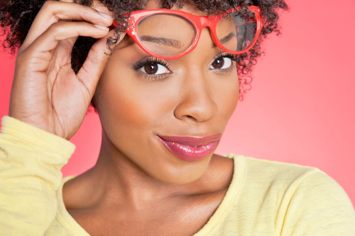 Black woman smiling while lifting her glasses off her nose.