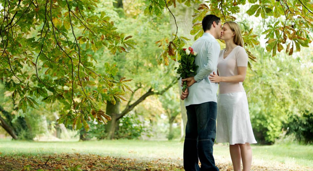 man with flowers behind his back kissing his girlfriend under a tree canopy